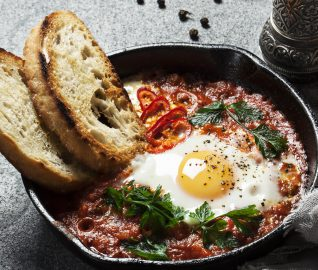 Shakshuka in a cast iron skillet on stone background