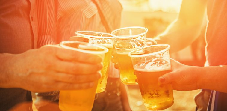 close up shot of hands toasting with beer. late afternoon with sunlight effect